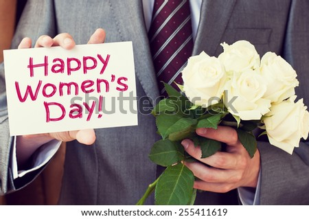 Happy Women's Day! Man wearing a suit holding a greeting card and white roses - stock photo