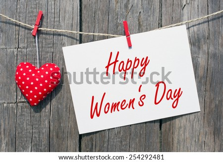 Happy Women's Day - white card with text and red heart on wooden background - stock photo