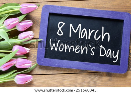 Happy Women's Day with tulips. Happy Women's Day on blackboard with pink tulips - stock photo