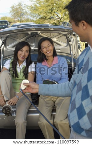 Happy women sitting in car's boot looking at man holding golf club - stock photo