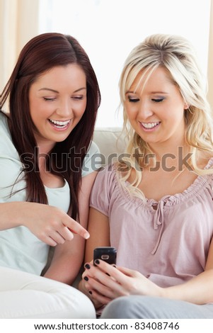 Happy women sitting on a sofa with a mobile in a living room