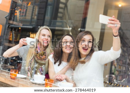 Happy women taking a selfie in a cafe in Copenhagen. They are in their twenties, enjoying a cup of coffee or tea and wearing smart casual clothes. - stock photo