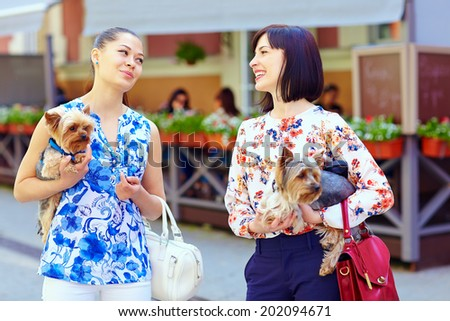 happy women talking on crowded city street, hold Yorkshire Terrier - stock photo
