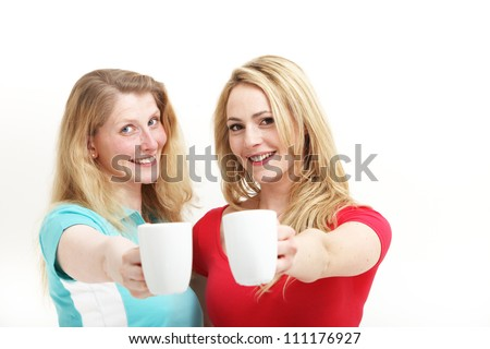 Happy women toasting with coffee Two happy attractive women smiling in amusement raising their mugs and toasting with coffee isolated on white
