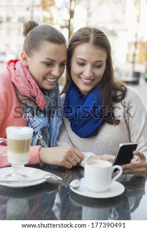 Happy women using cell phone at sidewalk cafe - stock photo