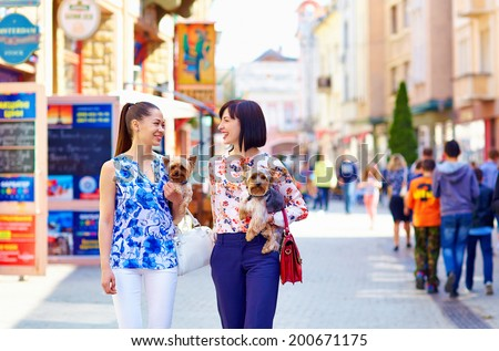 happy women walking the crowded city street, hold Yorkshire Terrier - stock photo
