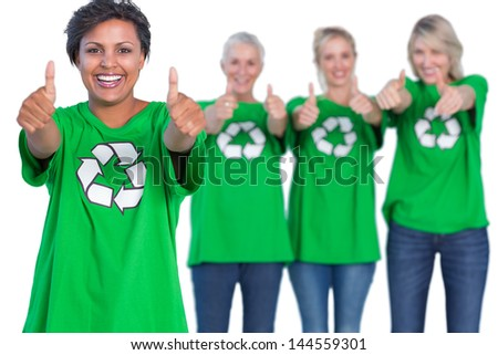 Happy women wearing green recycling tshirts giving thumbs up on white background - stock photo