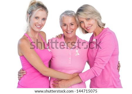 Happy women wearing pink tops and ribbons for breast cancer on white background - stock photo