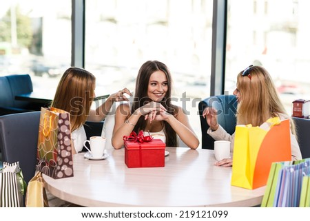 Happy women with coffee cup while looking at each other in cafe - stock photo
