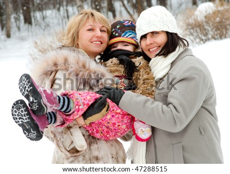 Happy women with daughter in winter outdoors