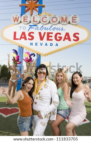 Happy women with Elvis impersonator in front of a sign