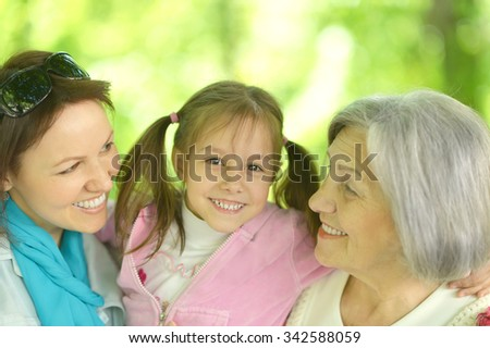 happy women with little girl in  park