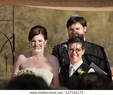 Happy women with rabbi in civil union ceremony - stock photo