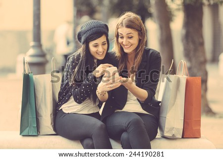 Happy Women with Smart Phone and Shopping Bags. They're looking at the same Smart Phone looking at Photos or Sending Messages. - stock photo
