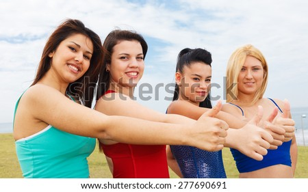 Happy women with thumbs up - stock photo