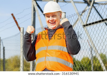 Happy worker at outdoors near the fence - stock photo