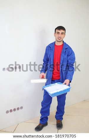 Happy worker in blue clothes stands with paint roller in new apartment - stock photo