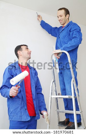 Happy workers in blue with construction tools, stand on ladder and look at each other in new apartment - stock photo