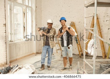 Happy workers standing at renovation site, smiling, looking at camera.
