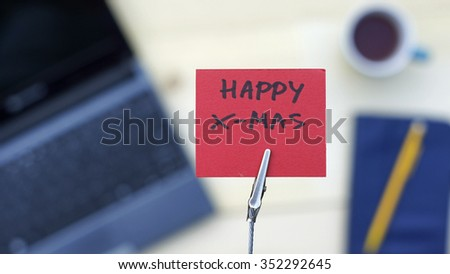 Happy X mas written on a memo at the office - stock photo