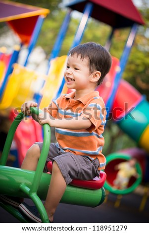 Happy 2 year old boy in an outdoor playground riding on a seesaw