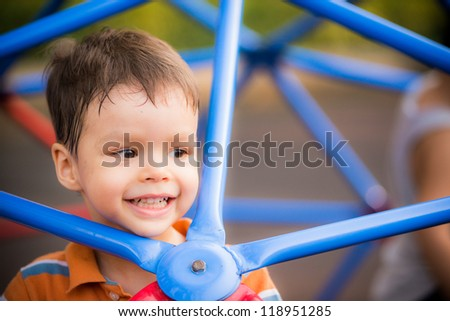 Happy 2 year old boy playing on blue bars in a playground - stock photo