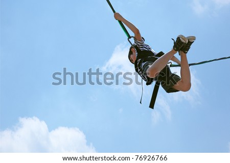 Happy 8 year old french-american boy bungee jumping against a blue and clouded sky with clipping path. - stock photo
