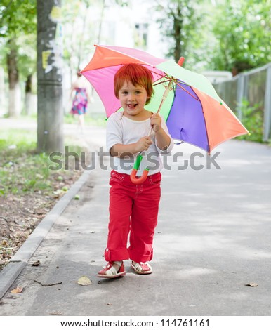 Happy 2 years girl  with umbrella in summer street