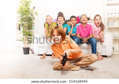 Happy 10 years old boy playing video games holding game controller sitting on floor with friends on background on white sofa in living room - stock photo