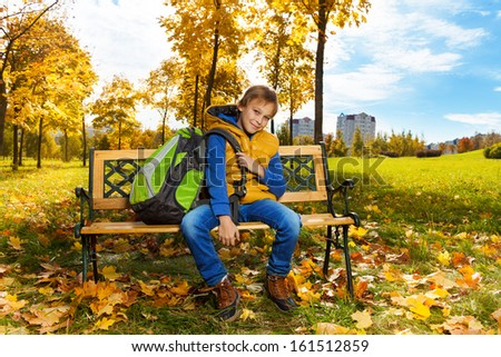 Happy 10 years old boy sitting on the bench with backpack after school with backpack on the shoulder - stock photo