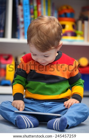Happy 2 years old boy using a digital tablet computer - stock photo