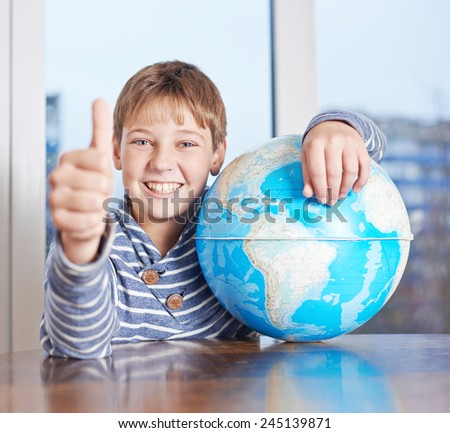 Happy 12 years old children boy sitting at the wooden desk holding a globe while showing a thumbs up gesture, composition against the window - stock photo
