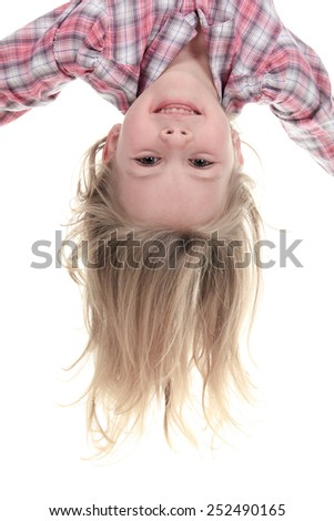 Happy 4 years old girl hanging upside down isolated on white with smile on her face - stock photo