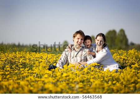 happy yong family having fun in the field of dandelions - stock photo