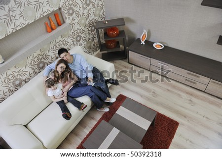 happy youg family relaxing in modern livingroom at home