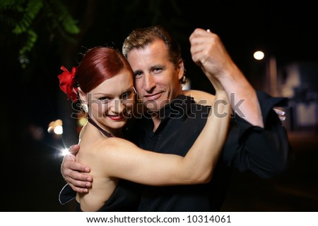 Happy young adult couple dancing outdoors at night, close-up - stock photo