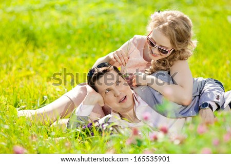 Happy young adult couple in love on the field. Two,  man and woman smiling and resting on the green grass.