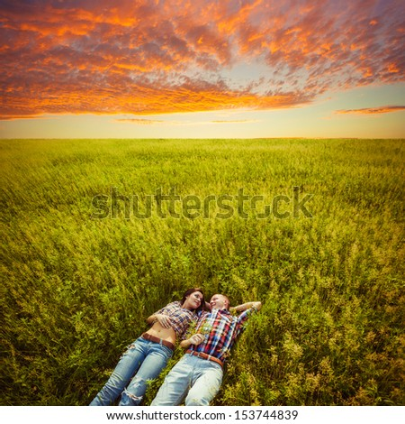 happy young adult couple lying on the grass over sunset - stock photo