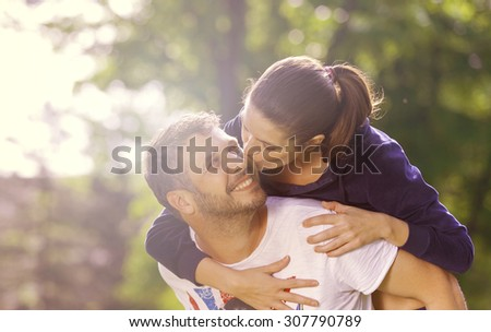 Happy young adult couple outdoors kissing and smiling, she holding on his back - stock photo
