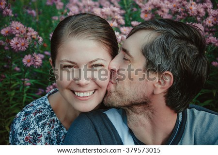 Happy young adult couple relaxing in the countryside, portrait - stock photo