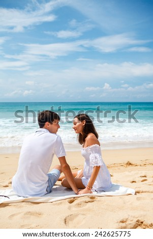 happy young adult couple sitting on a tropical beach - stock photo