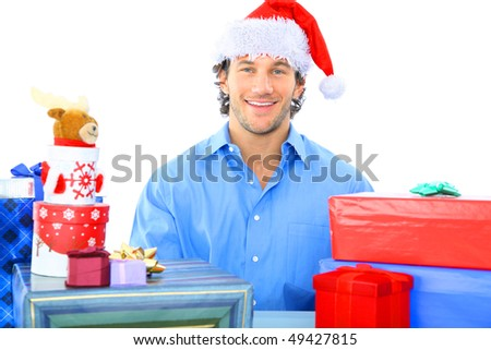 happy young adult wearing christmas santa hat with many gifts