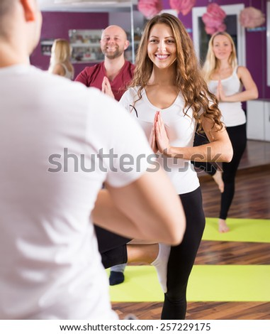 Happy young adults having yoga class in sport club - stock photo