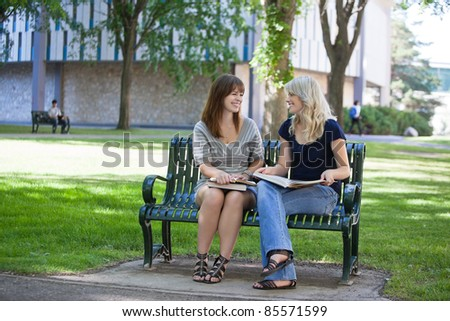 Happy young adults sitting on bench on college campus - stock photo