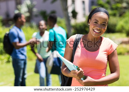 happy young African American college girl holding books - stock photo