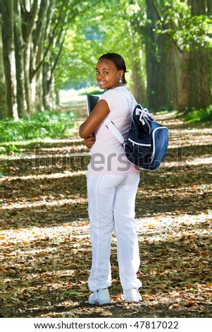 happy young african american college student in forest - stock photo