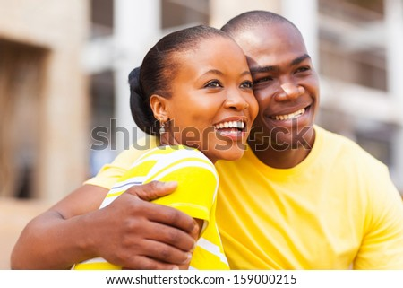 happy young african american couple outdoors looking away - stock photo