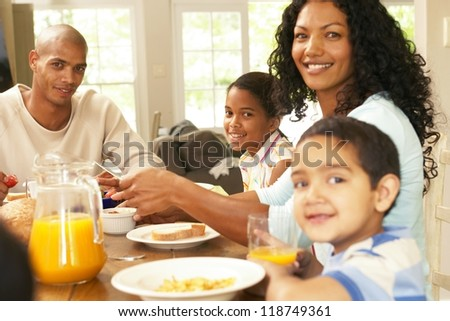 Happy young African American family seated around a table enjoying a healthy breakfast together in a relaxed start to the day - stock photo