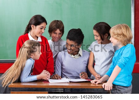 Happy young African American female teacher teaching schoolchildren at desk in classroom