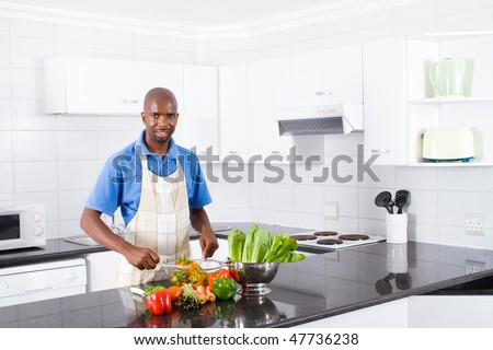 happy young african american man making a healthy salad in kitchen